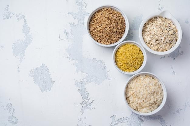 Varietà di fiocchi di cereali riso, miglio, grano saraceno, farina d'avena