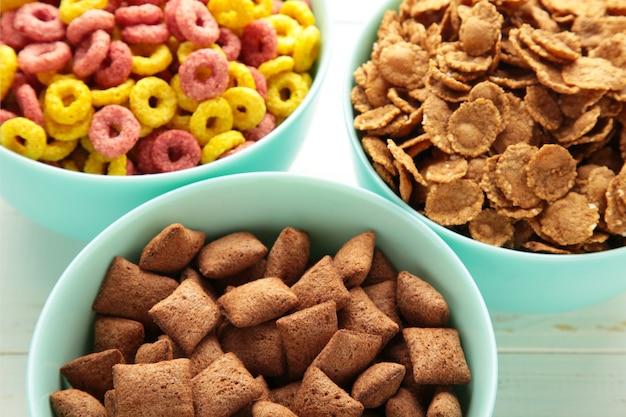 Varietà di cereali in ciotole blu, sfondo colazione veloce. vista dall'alto
