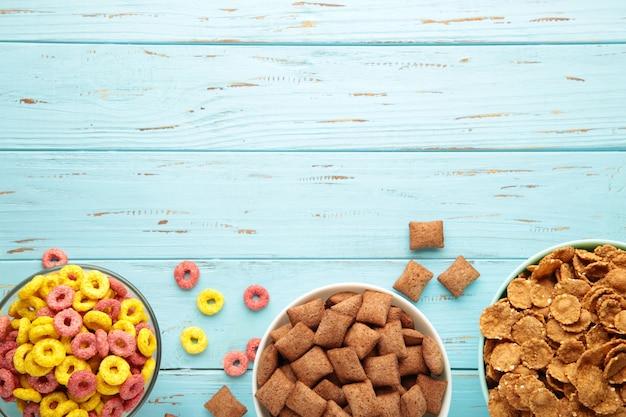 Varietà di cereali in ciotole blu, colazione veloce su fondo di legno blu. foto verticale