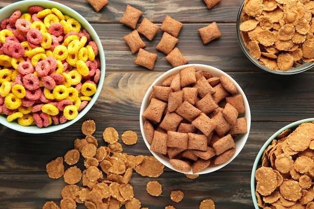 Varietà di cereali in ciotole blu, colazione veloce su fondo di legno marrone. vista dall'alto