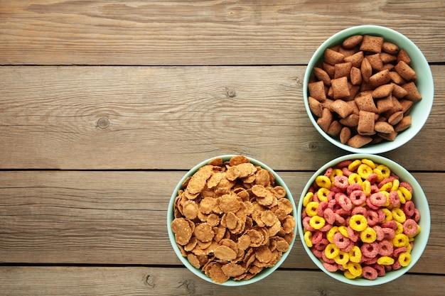 Varietà di cereali in ciotole blu, colazione veloce su fondo di legno grigio. foto verticale