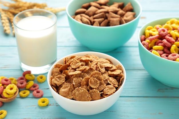 Varietà di cereali in ciotole blu, colazione veloce e latte su fondo di legno blu. vista dall'alto