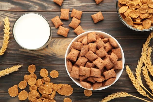 Varietà di cereali in ciotole blu, colazione veloce e latte su fondo di legno marrone. vista dall'alto