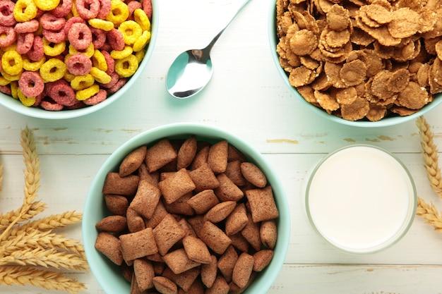 Varietà di cereali in ciotole blu, colazione veloce e latte su fondo di legno bianco.