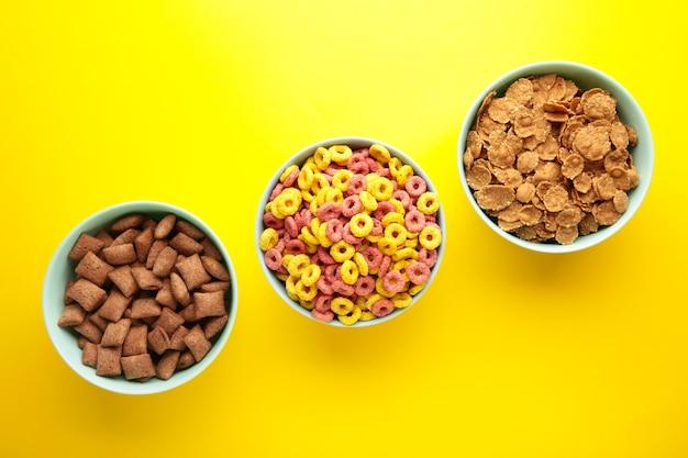 Varietà di cereali in ciotole blu, colazione veloce su sfondo giallo.