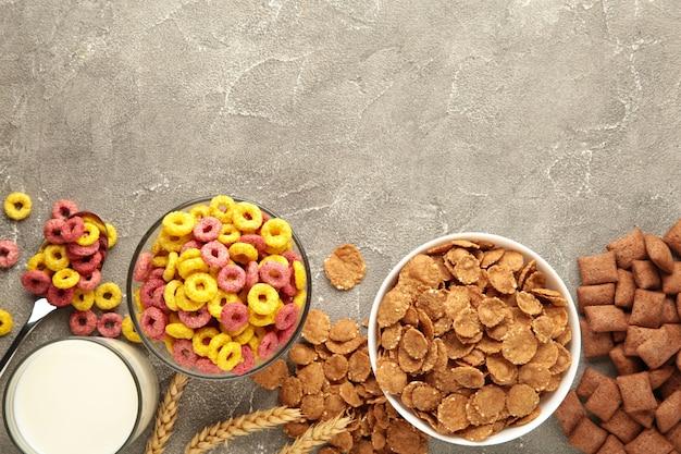 Varietà di cereali in ciotole, colazione veloce e latte su sfondo grigio. vista dall'alto