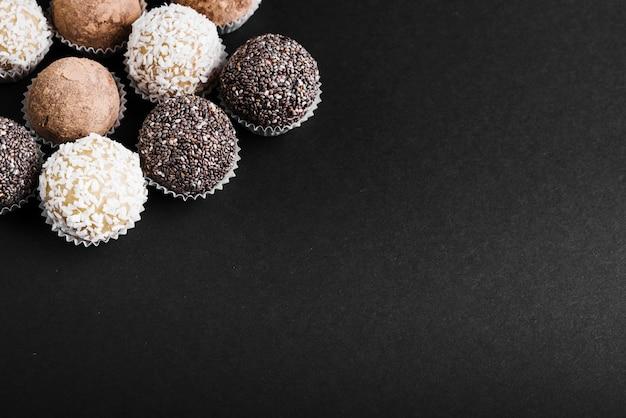 Varietà di palline di cioccolato su sfondo nero