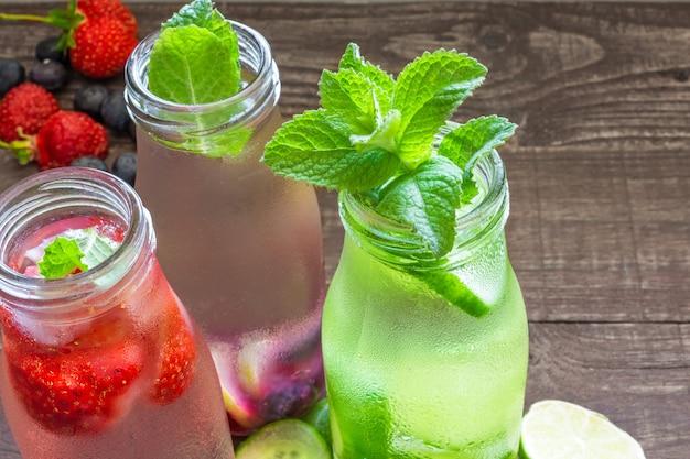 Varietà di bevande fredde estive in piccole bottiglie con frutta, bacche, cetrioli e menta
