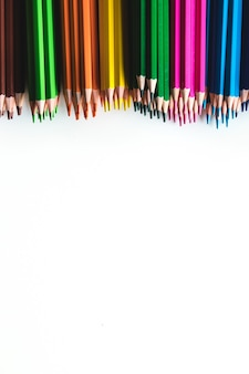 Varietà di matite colorate isolate su superficie bianca