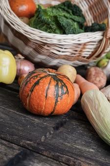 Varietà di verdure autunnali colorate sparse da un cesto di vimini su tavole di legno rustiche.