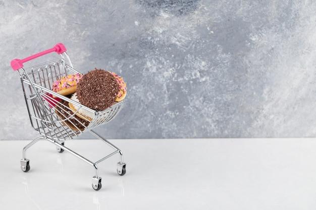 Varietà di biscotti sfoglia cremosi con codette in carrello di metallo