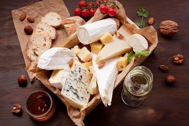 Varietà di formaggi diversi con vino, frutta e noci. camembert, formaggio di capra, roquefort, gorgonzolla, gauda, parmigiano, emmental