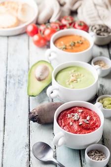 Varietà di zuppe di crema di verdure colorate differenti in ciotole. concetto di alimentazione sana o cibo vegetariano.