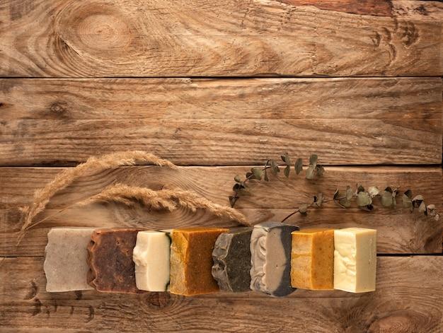 Varietà di barre di sapone fatte a mano differenti su fondo di legno.