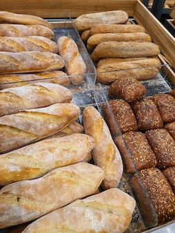 Varietà di diversi tipi di baguette di pane e panini per hot dog in panetteria o in drogheria fresca