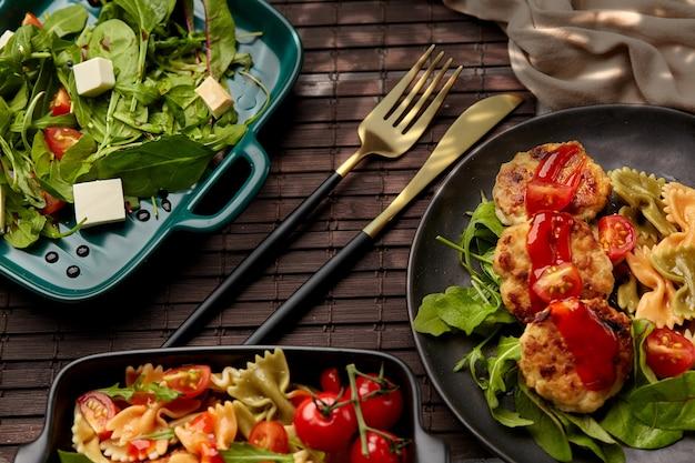 Una varietà di piatti su uno sfondo scuro con il bagliore del sole cotoletta di pollo tradizionale con erbe insalata di pomodorini verdure stufate con pezzi di filetto di pollo fritto in pastella