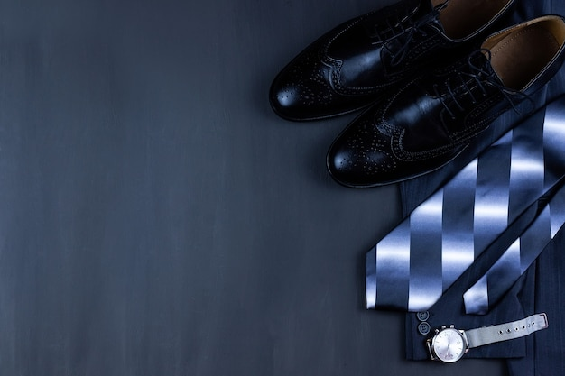 Varietà di abbigliamento da uomo formale closeup, giacca, orologio e cravatta su uno sfondo di legno nero