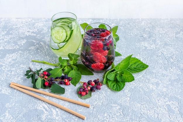 Varietà di bevanda fresca fresca detox con frutti di bosco e cetriolo. bicchieri di limonata o acqua per infusione aromatizzata, tè. una corretta alimentazione e una sana alimentazione. dieta fitness. copia spazio per il testo.