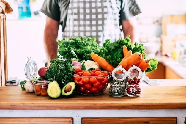 Varietà di frutta e verdura a casa o in un ristorante di cucina con un background di chef irriconoscibile