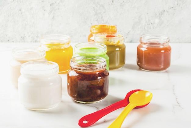 Varietà di purea di frutta e verdura casalinga per bambini, copyspace in marmo bianco