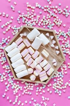 Varietà marshmallows tagliere di salumi su sfondo rosa. primo piano, vista dall'alto.