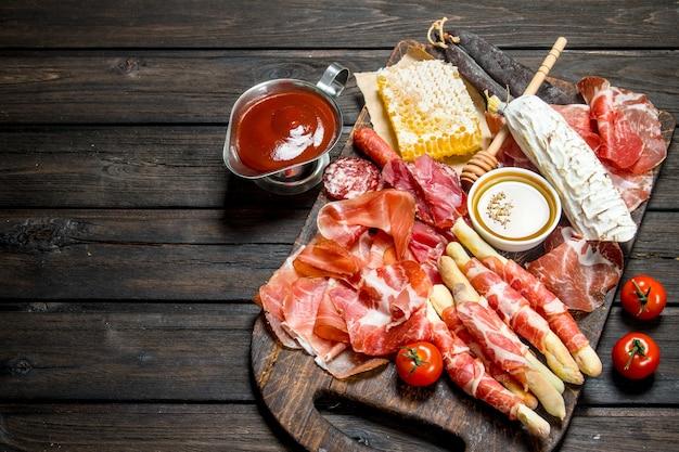 Una varietà di snack a base di carne su un tavolo rustico.