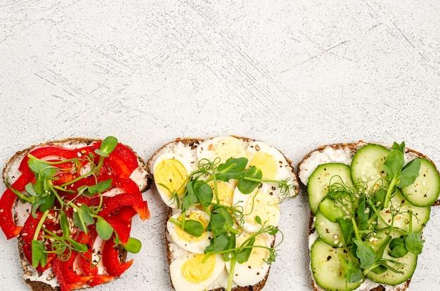 Varietà di mini panini con formaggio e verdure su una superficie leggera