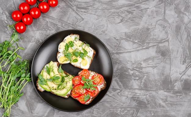 Varietà di mini panini con crema di formaggio e verdure in un piatto nero Foto Premium