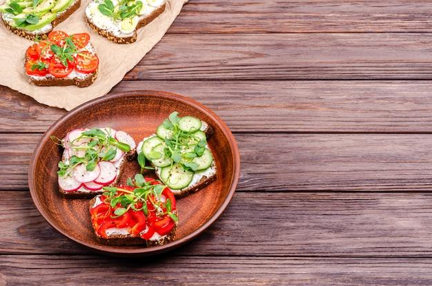 Una varietà di mini panini con crema di formaggio e verdure su una grattugia di argilla e carta su una superficie di legno