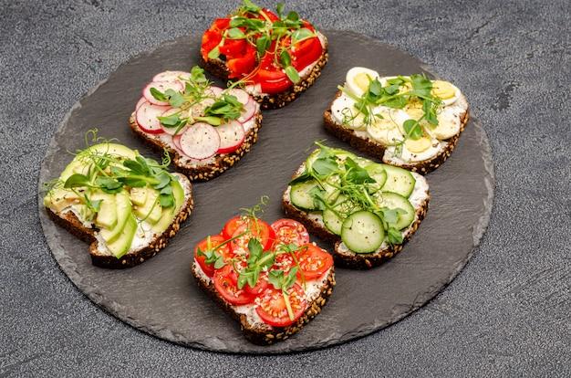 Varietà di mini panini con crema di formaggio e verdure su piastre su un bordo nero