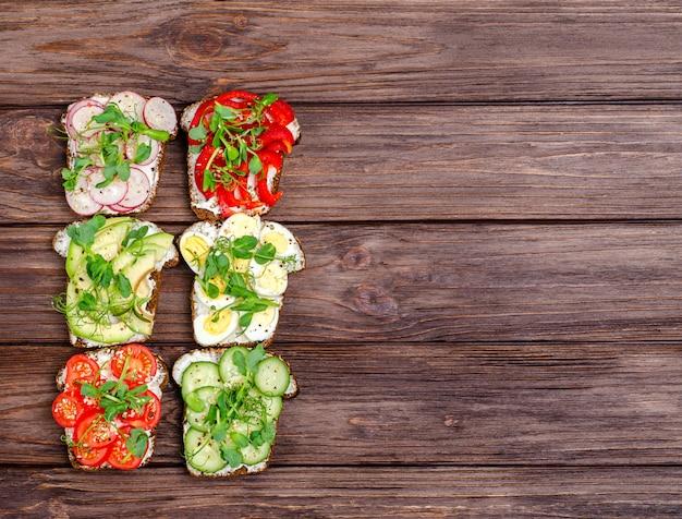 Varietà di mini panini con crema di formaggio e verdure su una superficie di legno