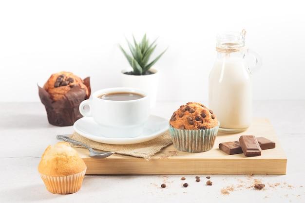 Varietà di muffin con una tazza di cioccolato al latte su una tavola di legno su uno sfondo bianco.