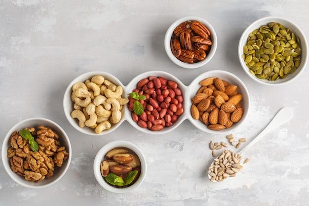 Una varietà di noci e semi in ciotole bianche, vista dall'alto, spazio di copia, sfondo di cibo. concetto di cibo vegetariano sano.
