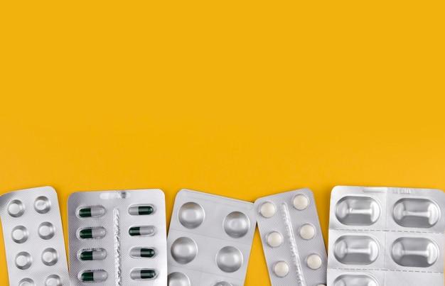 Una varietà di pillole in blister su uno spazio di copia muro giallo. medicinali