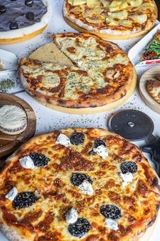 Varietà di pizze sul tavolo del ristorante da mangiare. immagine verticale