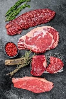 Varietà di bistecche di carne di manzo black angus crude filetto mignon, ribeye, controfiletto e gonna o machete. sfondo scuro. vista dall'alto.