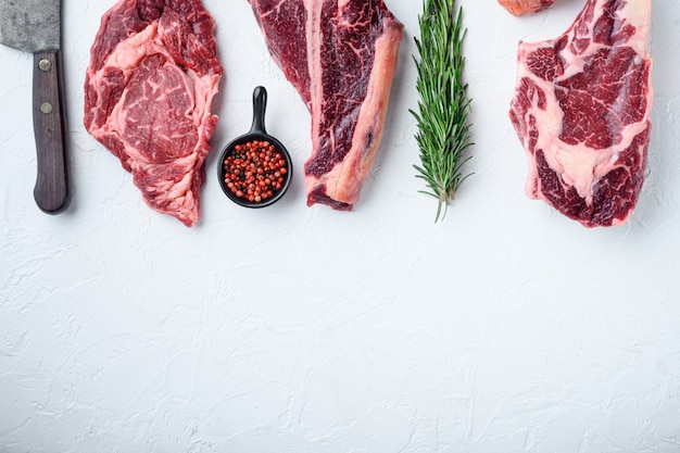 Varietà di bistecche di carne cruda black angus prime, tomahawk, t bone, bistecca club, costata e tagli di filetto, su pietra bianca
