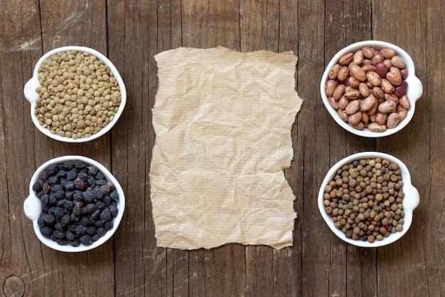 Varietà di legumi asciutti crudi e spazio della copia su carta fra la vista superiore