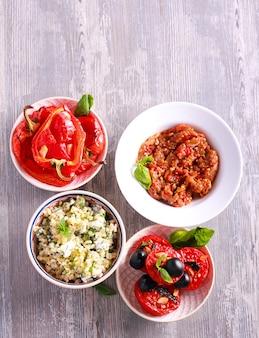 Varietà di insalate e antipasti sui piatti, vista dall'alto