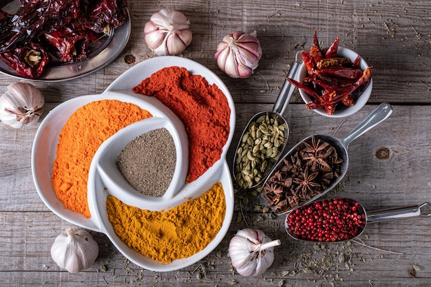 Varietà di spezie ed erbe aromatiche di colori esotici indiani, sul tavolo della cucina