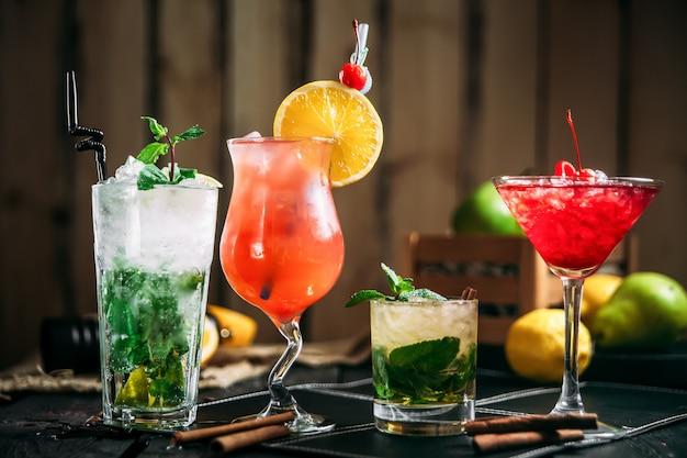 Varietà di cocktail alcolici dolci in diversi bicchieri, mojito, mai tai, cosmopolita e sesso in spiaggia, vista laterale, orizzontale