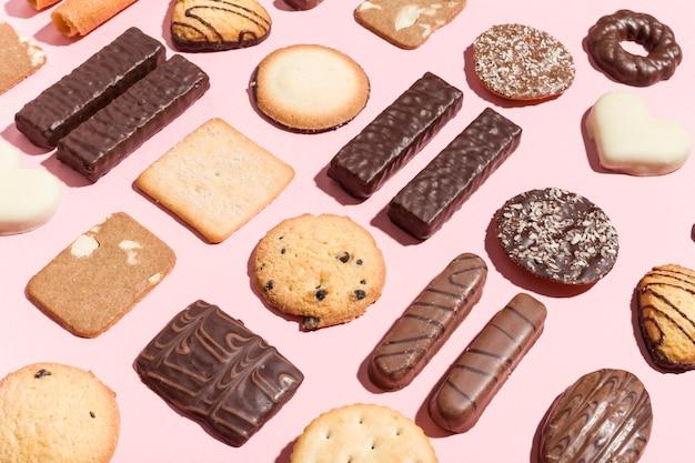 Varietà di biscotti tradizionali disposti geometricamente su sfondo rosa