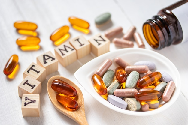 Varietà di pillole vitaminiche su legno bianco