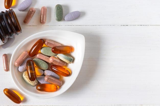 Varietà di pillole vitaminiche su fondo di legno bianco, prodotto supplementare e sanitario, superficie piana
