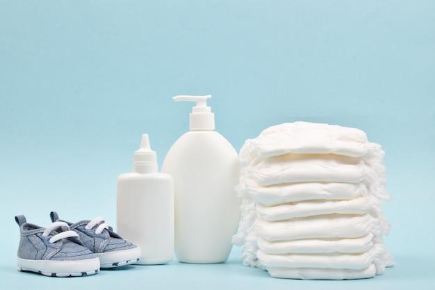 Vari accessori per l'igiene dei bambini. una grande pila di pannolini accanto a loro sono bottiglie di cosmetici per bambini. copia spazio