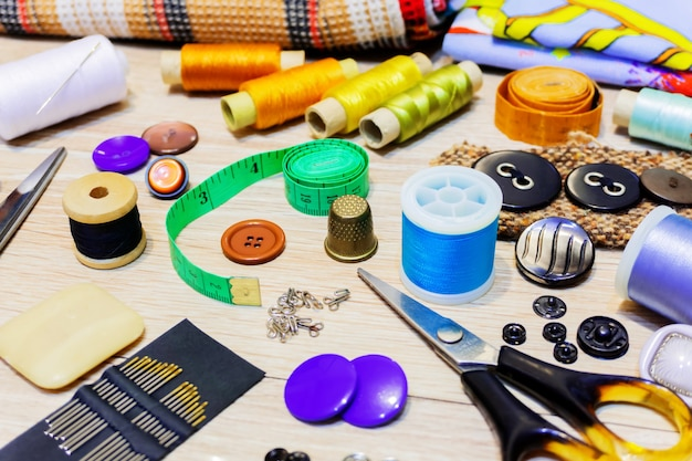 Vari accessori per il cucito e il ricamo giacciono sul tavolo