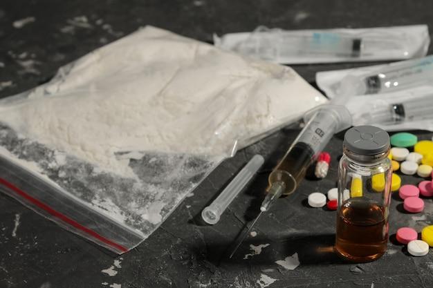 Varie droghe che creano dipendenza. cocaina, eroina e pillole su un tavolo nero. il concetto di tossicodipendenza.