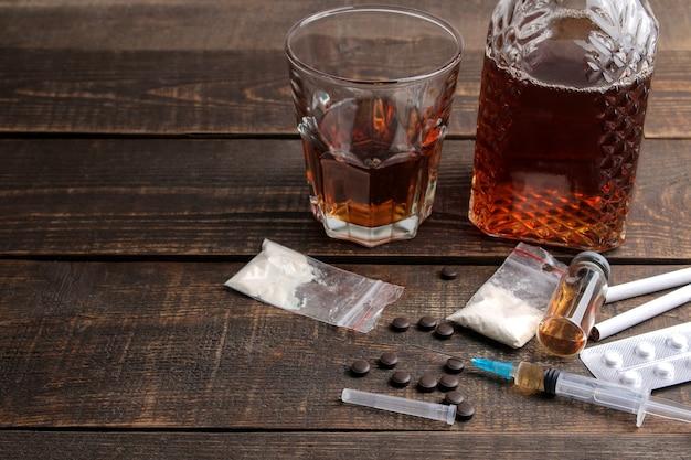 Varie droghe che creano dipendenza tra cui alcol, sigarette e droghe su un tavolo di legno marrone. concetto di tossicodipendenza