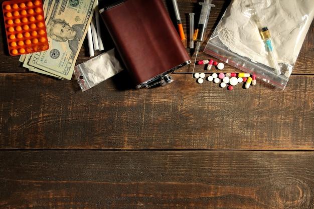 Varie droghe che creano dipendenza tra cui alcol, sigarette e droghe su un tavolo di legno marrone. vista dall'alto con posto per il testo.