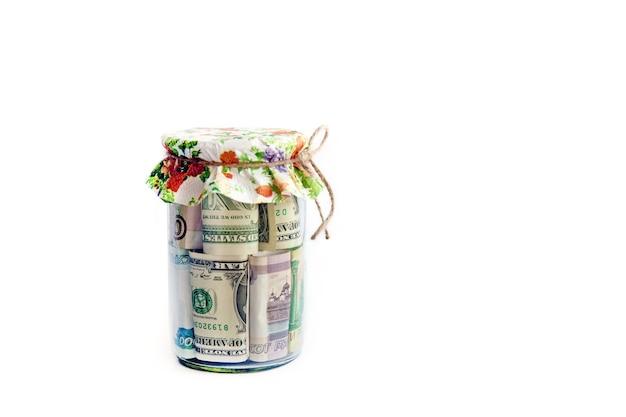 Varie banconote sono arrotolate in un barattolo di vetro coperto con un tovagliolo colorato su sfondo bianco